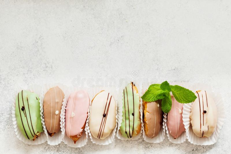 Top view of cute mini eclair cakes in pastel colors garnished wi royalty free stock photos