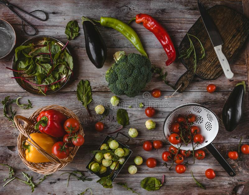 top view of cutting board, knife, eggplants, wicker basket, plate, colander, cherry tomatoes, peppers, mangold leaves, broccoli royalty free stock photos