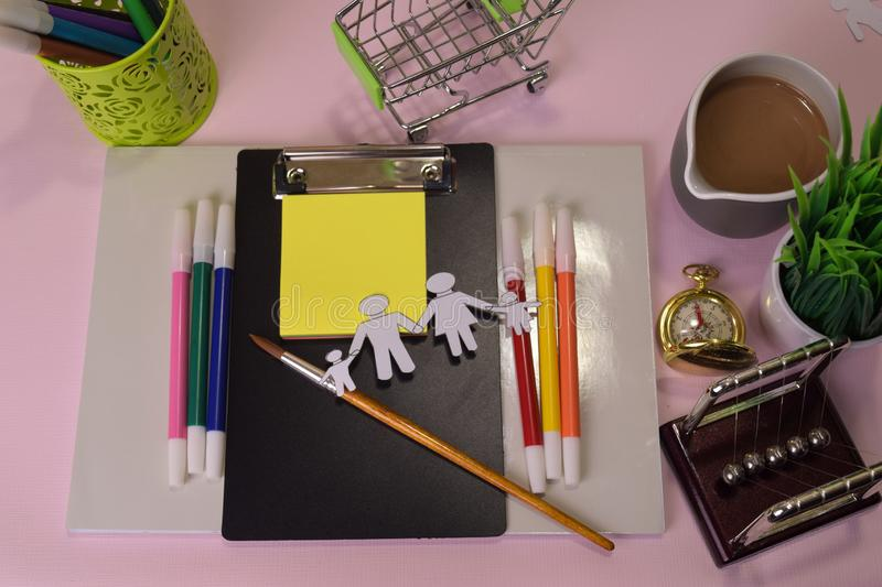 Top view of the cutting paper illustration a family on a pink table, preparing to do homework in a clipboard. Drawing Working Desk royalty free stock photos