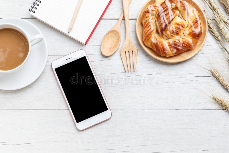 Top view danish pastries, coffee, note book and smartphone on white wooden table stock photos