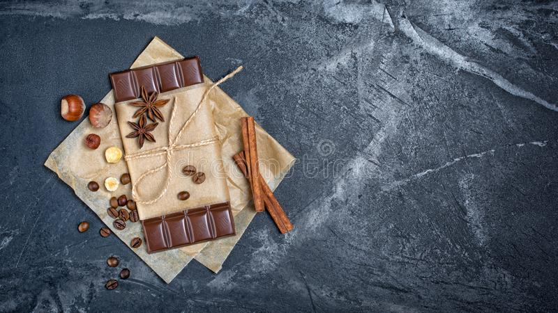 Top view of dark chocolate bar with coffee beans, whole hazelnuts and spices as cinnamon sticks and anise stars royalty free stock photography