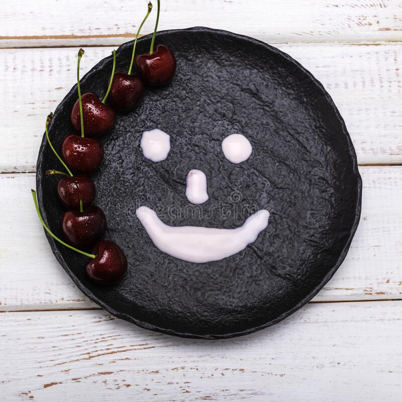 Top view of a dark plate with red cherry berries, everything is on a light wooden surface and a yogurt face is drawn on the plate. Medium top view of a dark stock photos