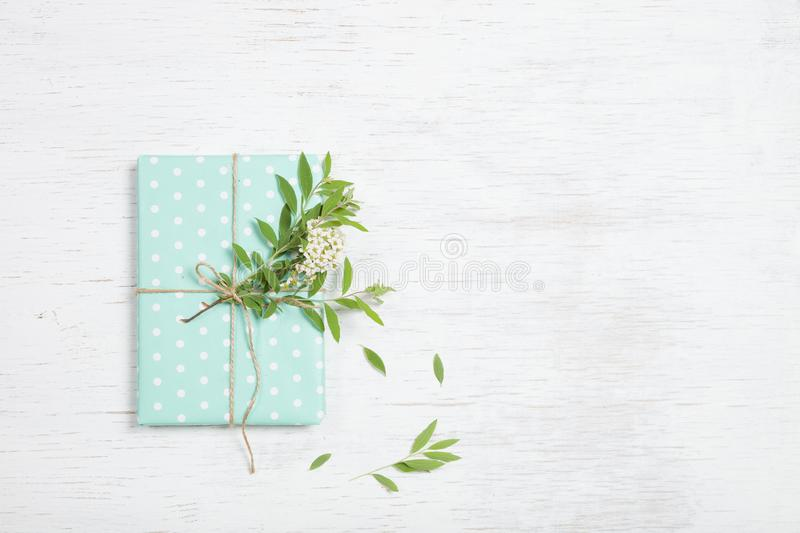 Top view on decorated birthday gift with garden tree branch and flowers. Packing present for the party. Flat lay. stock photo
