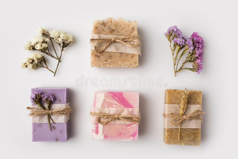 Homemade soap with flowers. Top view of decorated homemade soap with flowers on white surface royalty free stock photo