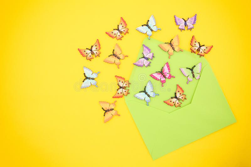 Top view of decorative, multicolored butterflies comming out of an open, green envelope from recycled paper on a vibrant yellow royalty free stock photography
