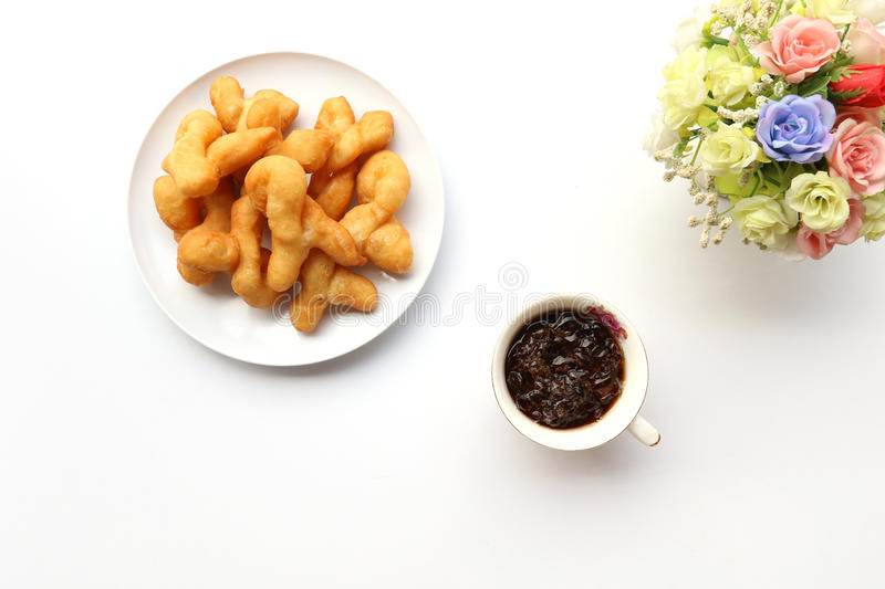 Top view of deep-fried dough stick with cold coffe and flower in. Jar on white background royalty free stock photos