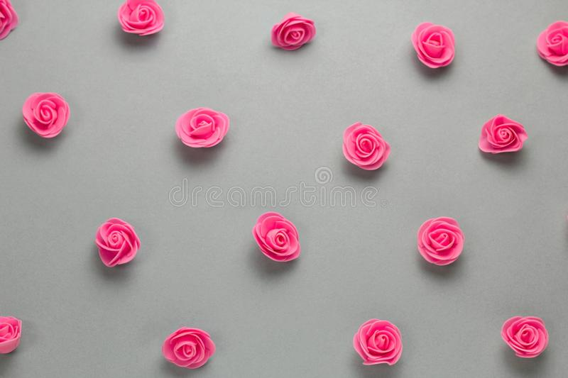 Delicate pink roses buds pattern on a gray background. Top view delicate pink roses buds pattern on a gray background stock images