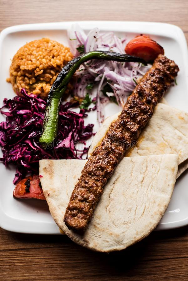 Top view of a delicious adana kebab. With bulgur, cabage salad and zataar onion stock image