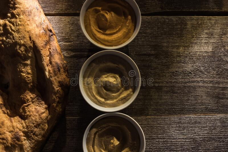 Top view of delicious assorted hummus and fresh baked pita on wooden rustic table. royalty free stock images