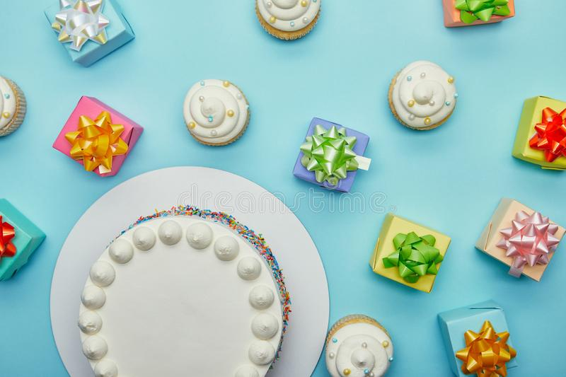 Top view of delicious cake, cupcakes and gifts. On blue background stock photography
