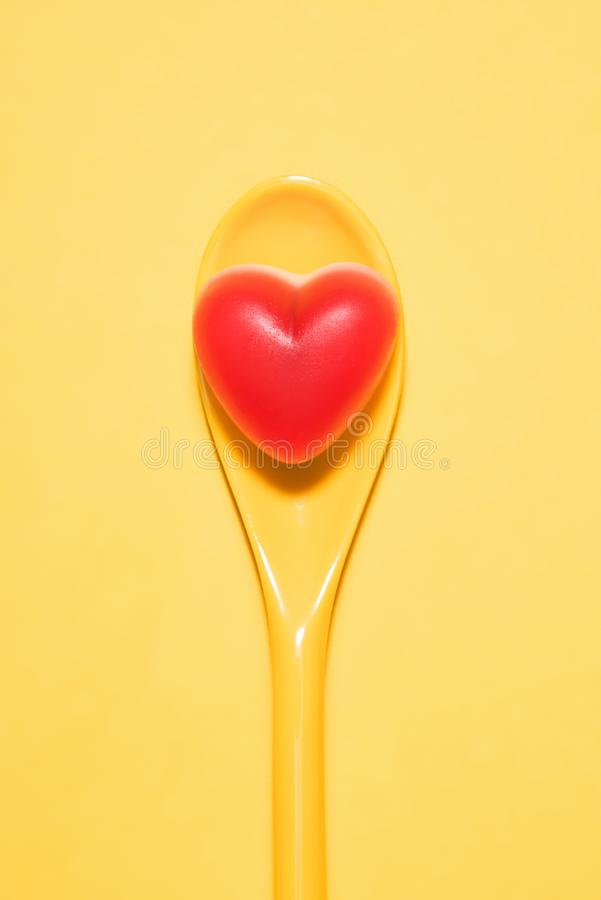 top view of delicious candy in shape of red heart on spoon and stock image