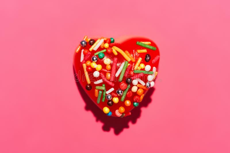 Top view of delicious candy in shape of red heart with sprinkles. On pink stock images