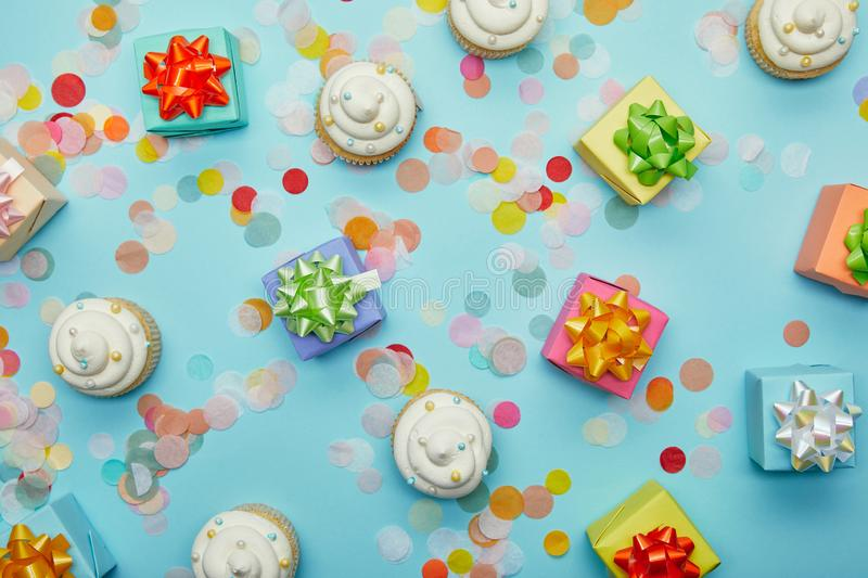 Top view of delicious cupcakes, confetti and gifts. On blue background stock photography