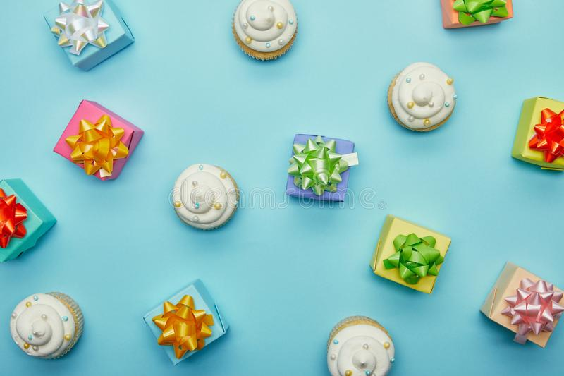 Top view of delicious cupcakes and gifts. On blue background royalty free stock photos