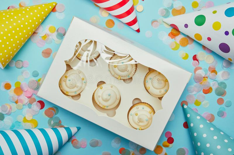 Top view of delicious cupcakes, party hats and confetti. On blue background stock photos