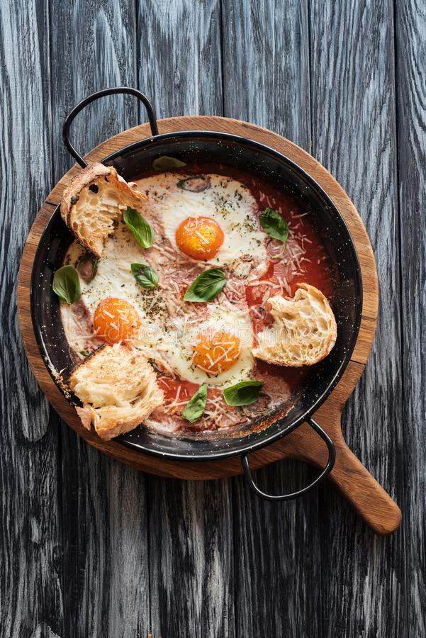 Top view of delicious fried eggs with cheese, bread and sauce in pan on wooden. Cutting board stock photo
