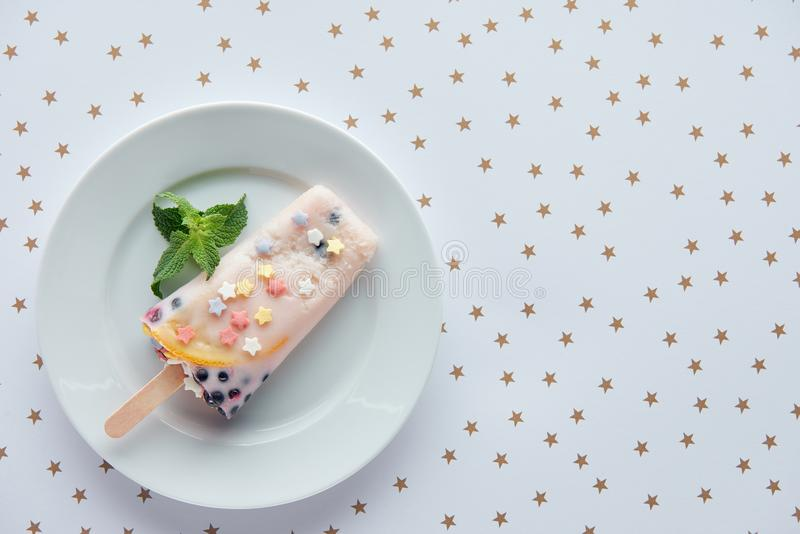 top view of delicious fruity popsicle with mint leaves on plate and beautiful golden stars royalty free stock photography