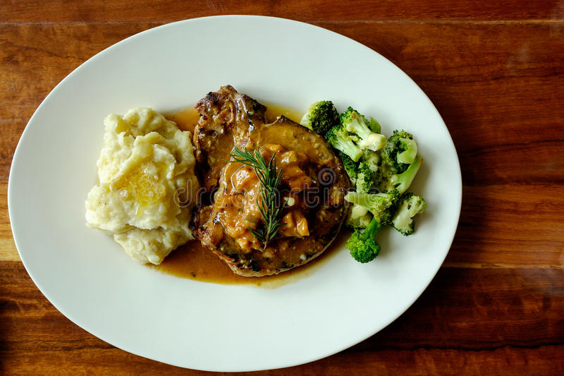 Top view of delicious grilled pork chops with mash potato and steamed green broccoli on brown wood table. The image of Top view of delicious grilled pork chops royalty free stock photos