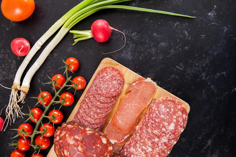 Top view of delicious healthy meat appetizers on wooden board royalty free stock photography