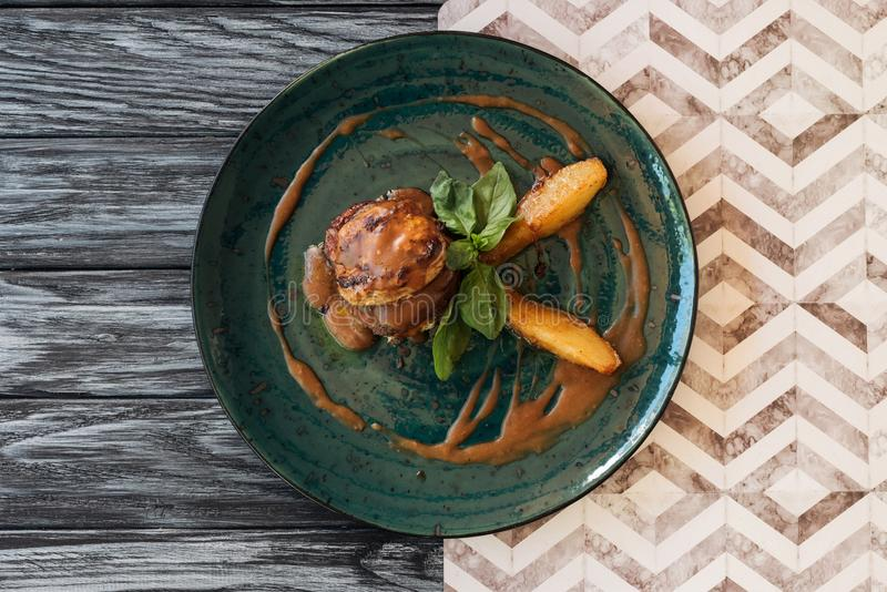 top view of delicious meat with sauce and basil leaves on plate royalty free stock photo