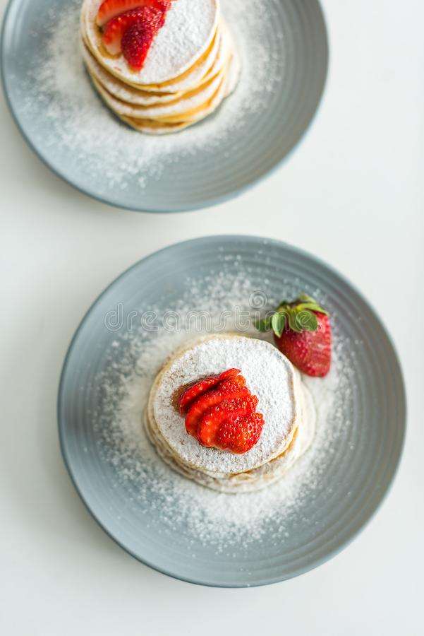 top view of delicious pancakes with ripe strawberries on table stock photo