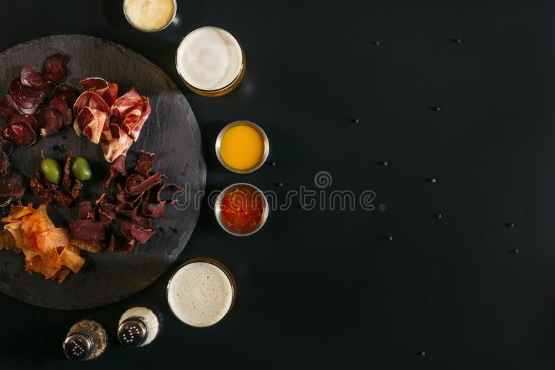 top view of delicious sliced assorted meat, glasses of beer, sauces and spices royalty free stock photos