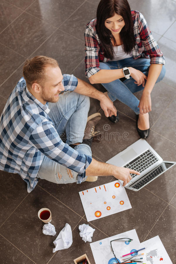 Top view of delighted positive colleagues sitting on the floor. Young designers. Top view of delighted positive friendly colleagues sitting on the floor and stock photos