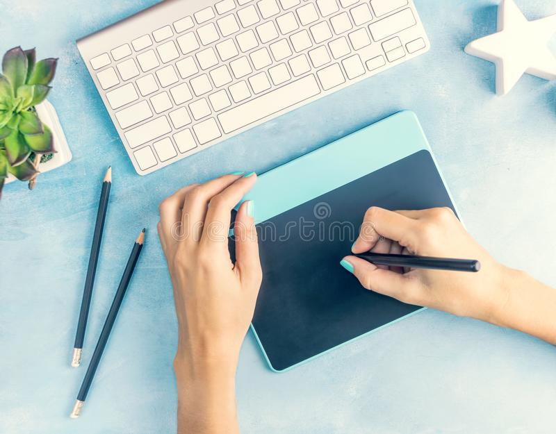 Top view designer`s hands working with graphic tablet on blue table stock photo