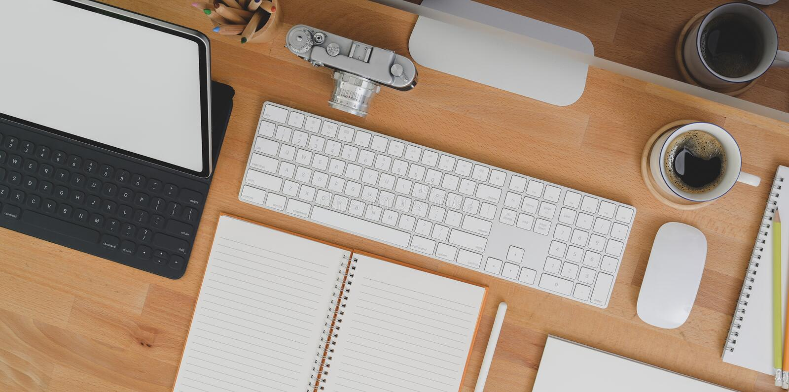 Top view of designer workplace with tablet, blank notebook office supplies on wooden table. With copy space royalty free stock photography