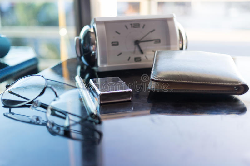 Top view desk in bedroom and on table have glasses ,clock ,wallet ,note ,fire and passpost. royalty free stock images