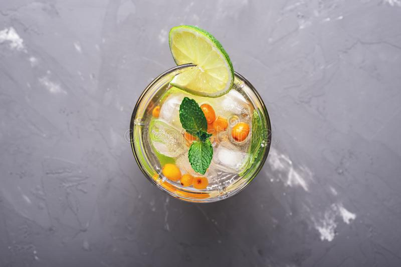Top view on detox summer cocktail of sea buckthorn, lime and mint with ice cubes in the water royalty free stock photography