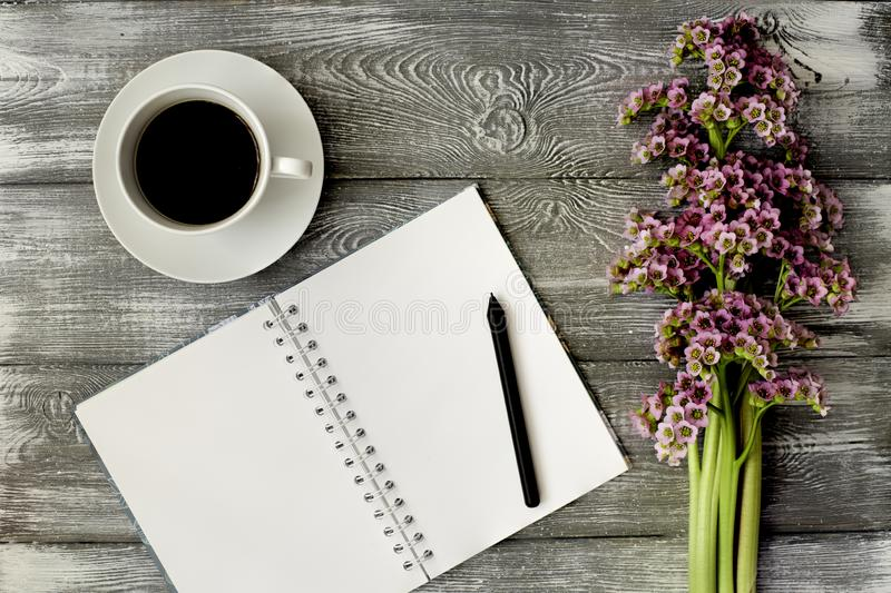 Top view of a diary or notebook, pen and coffee and a purple flower on a gray wooden table. Flat design. stock images