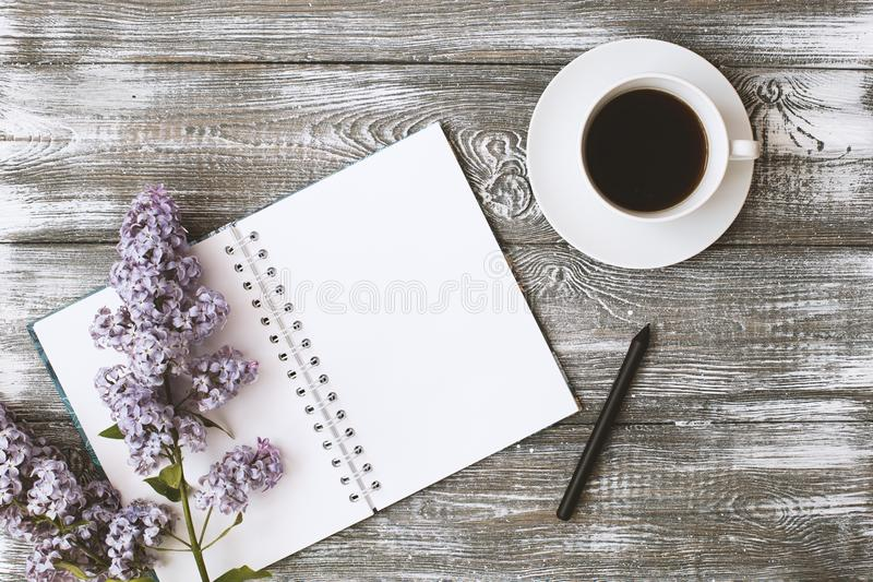 Top view of a diary or notebook, pencil and coffee and a purple flower on a gray wooden table. Flat design. stock image