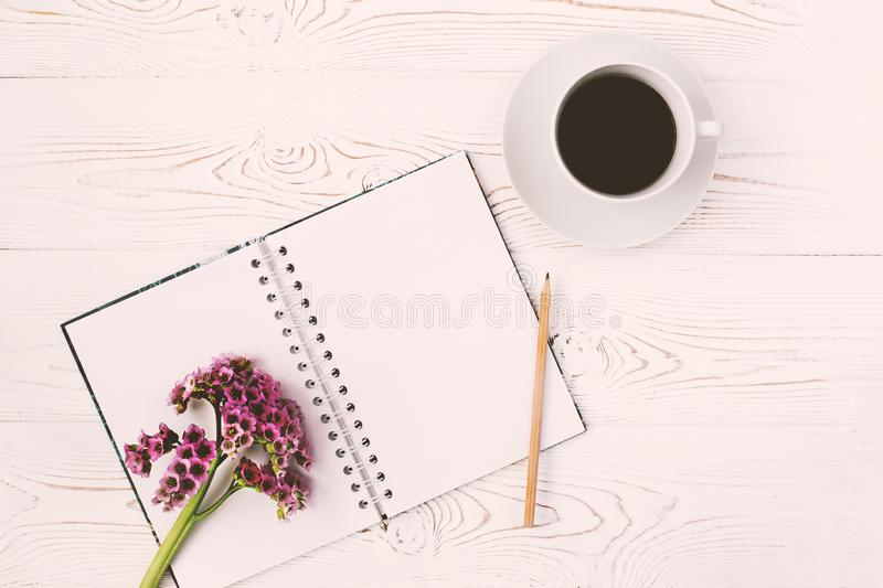 Top view of a diary or notebook, pencil and cup of coffee and a purple flower on a white wooden table. Flat design stock photos