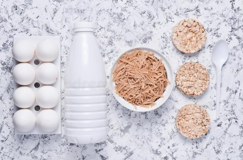 Top view of diet, healthy food. Crispy round dietary fitness bread, bottle of yogurt, buckwheat noodles, plastic egg tray. On a white concrete background. Flat stock photos
