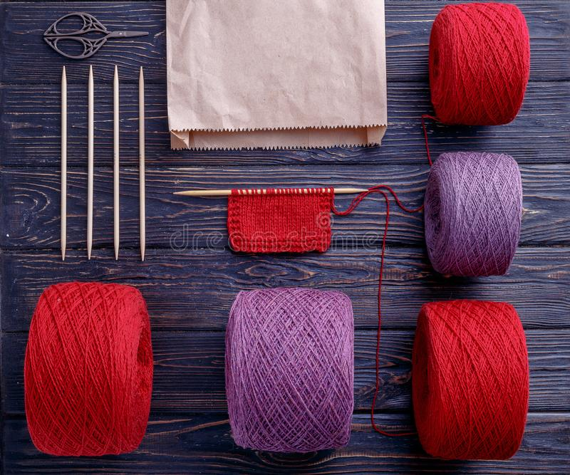 Top view of different knitting yarn. Knitting needles and knitting accsesories with paper bag on wooden background. Knolling yarn. Flatlay royalty free stock image