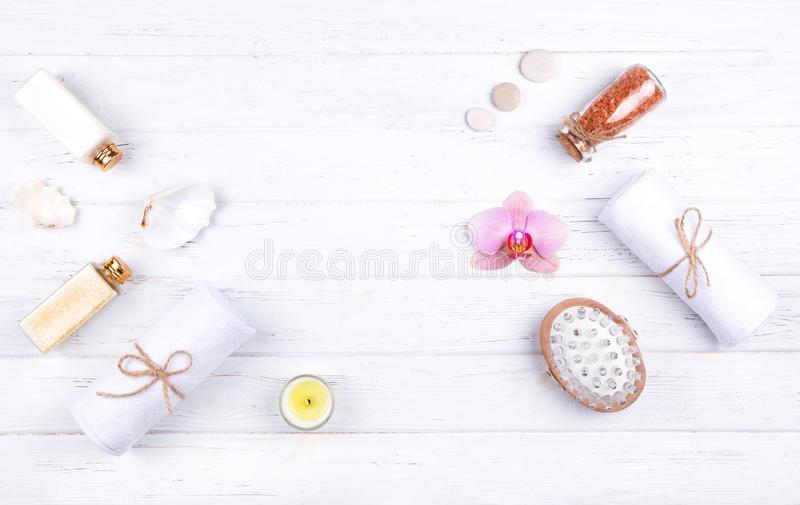 Different spa, beauty and wellness products: cream, balsam, sea salt in glass bottles, towels, massage brush royalty free stock images