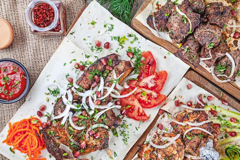Top view on different types of meat. Food party table. Many different dishes. Steak barbecue, grilled chicken and pork with red stock photo