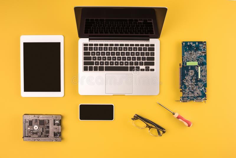 Top view of digital devices with black screens and motherboard and hardware. On yellow stock photos