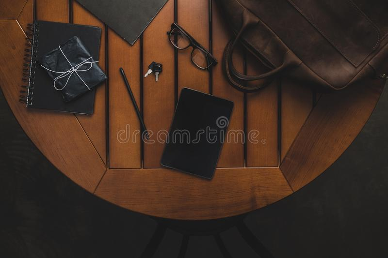Top view of digital tablet, leather bag, eyeglasses and keys. On wooden table stock images