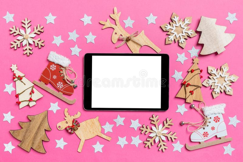 Top view of digital tablet, pink background decorated with festive toys and Christmas symbols reindeers and New Year trees. stock photo