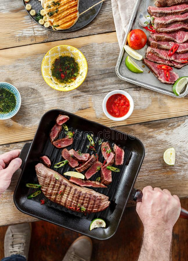 Top view dinner table concept Beef steak grill chicken steak grill wooden table sauces sunny evening stock images