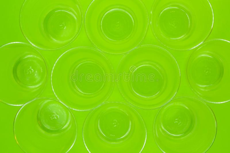 Top view of disposable empty transparent plastic cups on green background. Recycling waste stock image