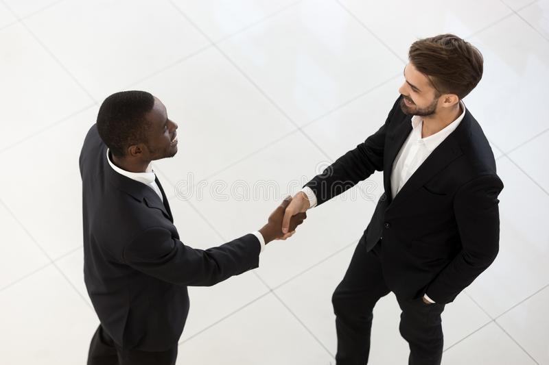 Top view of diverse male employees handshake talking in hallway royalty free stock photo