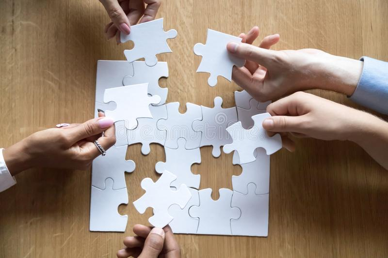 Top view of diverse people assemble jigsaw looking for solution. Top view of hands of diverse people assemble jigsaw helping each other looking for right royalty free stock photos
