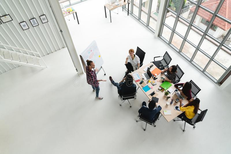 Top view of diverse people of creative team group using smartphone, mobile phone, tablet and computer laptop while meeting. stock images