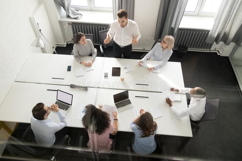 Overhead view busy multi racial office workers brainstorming at boardroom. Top view diverse workers and clients gather at modern boardroom discuss new project stock images