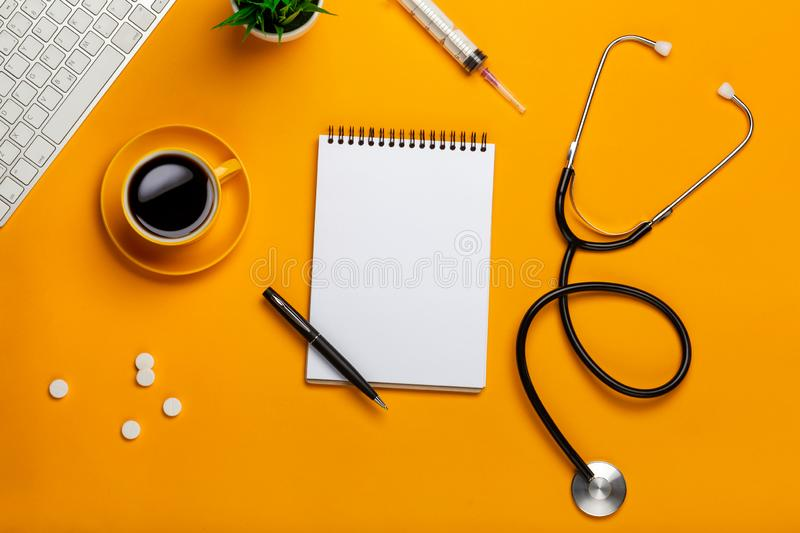 Top view of a doctor`s table with notepad and pen stethoscope, keyboard, prescription and pills, a cup of coffee on a yellow stock photo