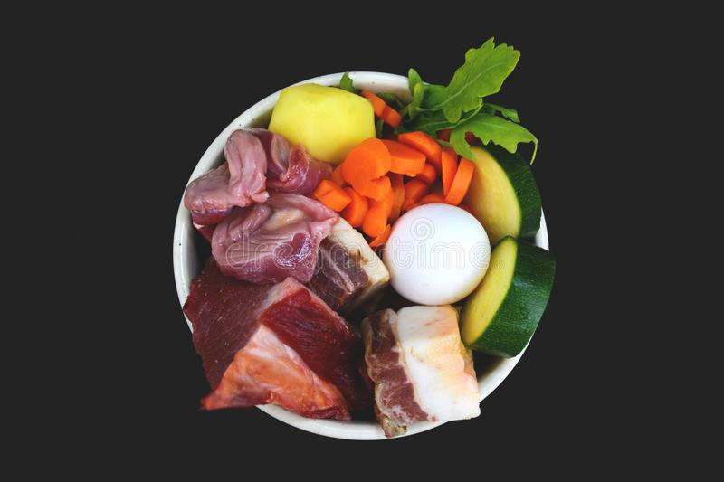 Top view of dog bowl filled with mixture of biologically appropriate raw food containing meat chunks, vegetables, egg royalty free stock photo