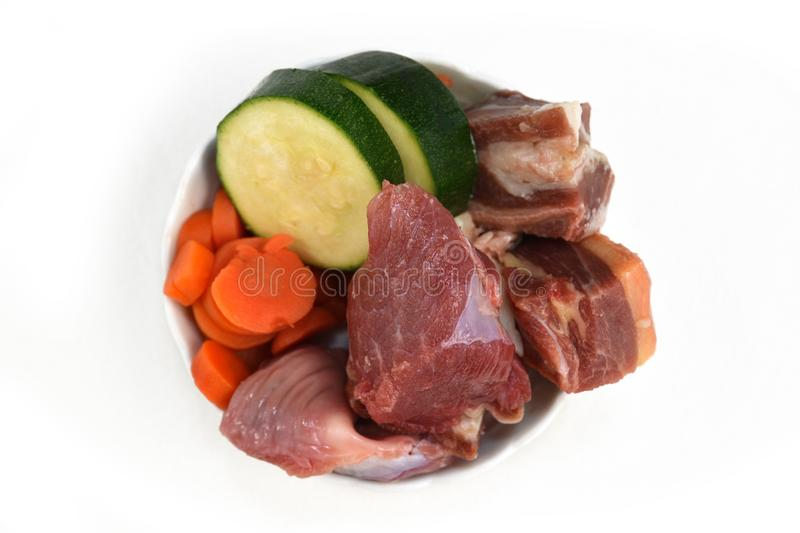 Dog bowl filled with mixture of biologically appropriate raw food containing meat chunks and vegetables royalty free stock images